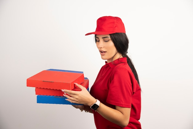 Surprised delivery woman looking at pizza boxes.