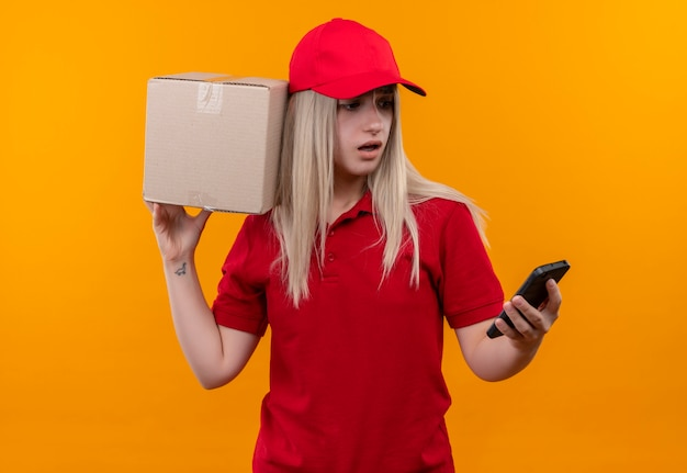 Удивленная девушка-доставщик в красной футболке и кепке, держащая коробку на плече, смотрит на телефон на руке на изолированном оранжевом фоне