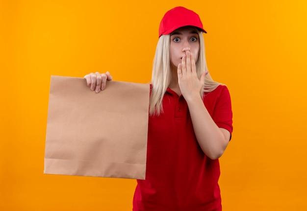 격리 된 오렌지 배경에 손으로 빨간 티셔츠와 종이 주머니를 들고 모자를 입고 놀란 배달 어린 소녀 덮여 입