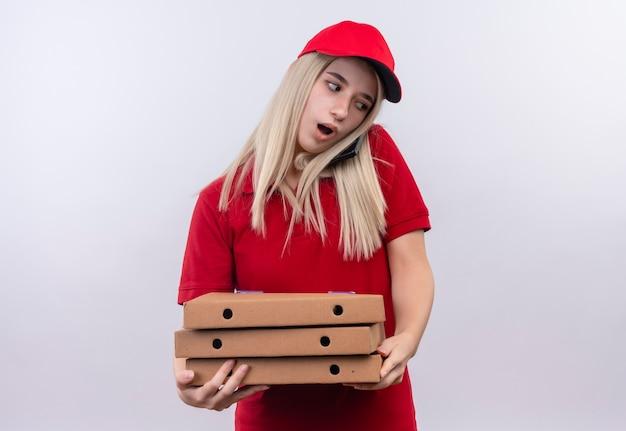Ragazza sorpresa di consegna che porta la maglietta rossa e la scatola della pizza della tenuta del cappuccio e parla sul telefono su fondo bianco isolato