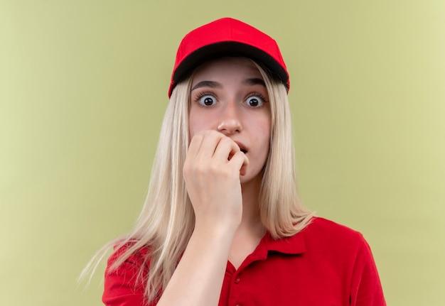 모자에 빨간 티셔츠를 입고 놀란 배달 어린 소녀 격리 된 녹색 배경에 입에 그녀의 손을 넣어