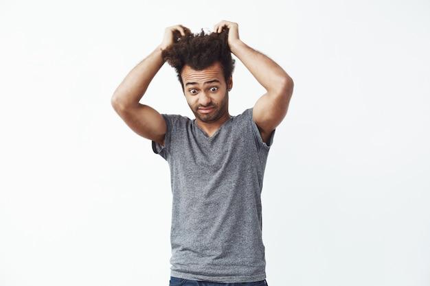 Surprised displeased african man looking down touching hair.