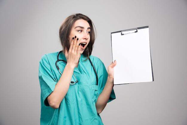 Удивленный доктор показывая доску сзажимом для бумаги на сером фоне. фото высокого качества