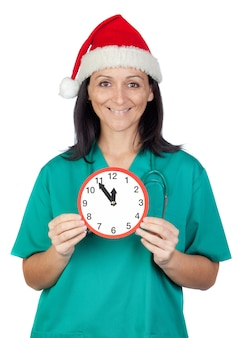 Surprised doctor woman with christmas hat and a clock isolated on white