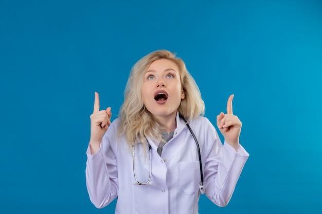 Stetoscopio da portare sorpreso della ragazza del medico in indumento medico indica su su fondo blu