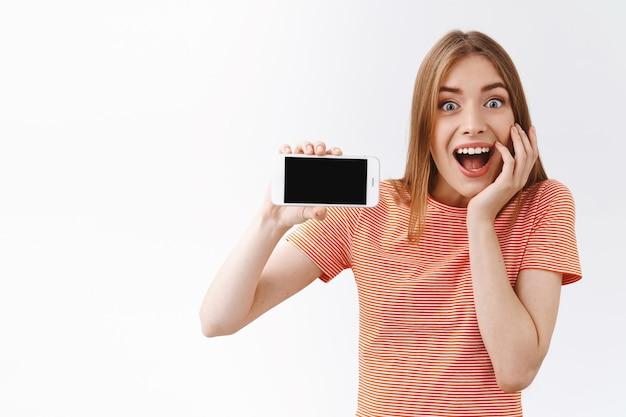 Удивленная, энергичная и восторженная красивая молодая кавказская женщина в полосатой футболке, держащая смартфон горизонтально, демонстрируя черный мобильный дисплей и тронувшись щекой от изумления и радости