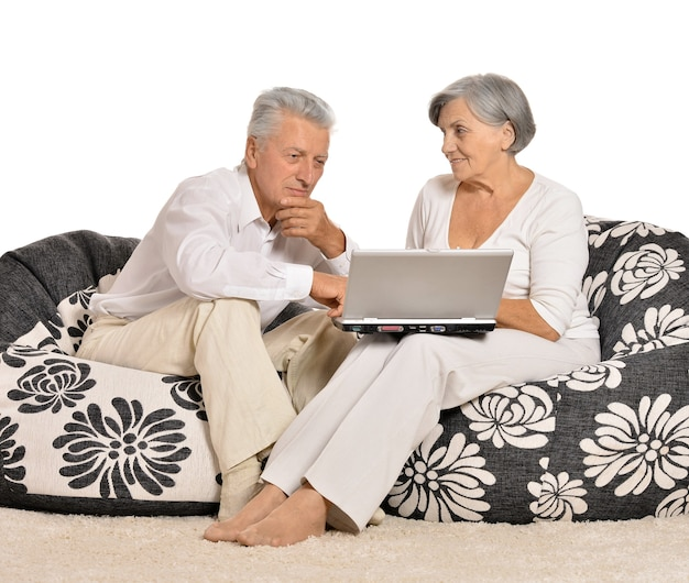 Surprised elderly couple looking on laptop screen on white background