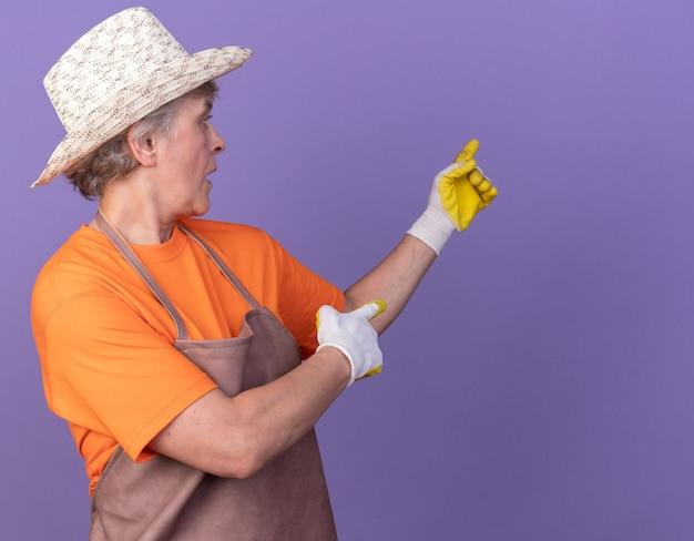 コピースペースで紫色の壁に隔離された側を見て、指しているガーデニングの帽子と手袋を身に着けている驚いた年配の女性の庭師