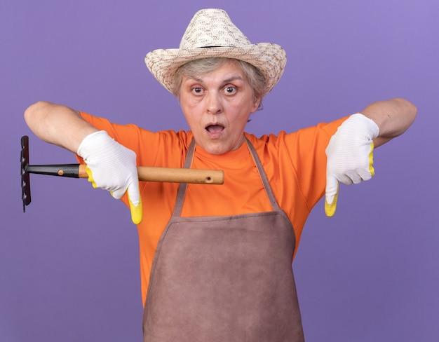 Il giardiniere femminile anziano sorpreso che indossa il cappello e i guanti di giardinaggio indica giù che tiene rastrello