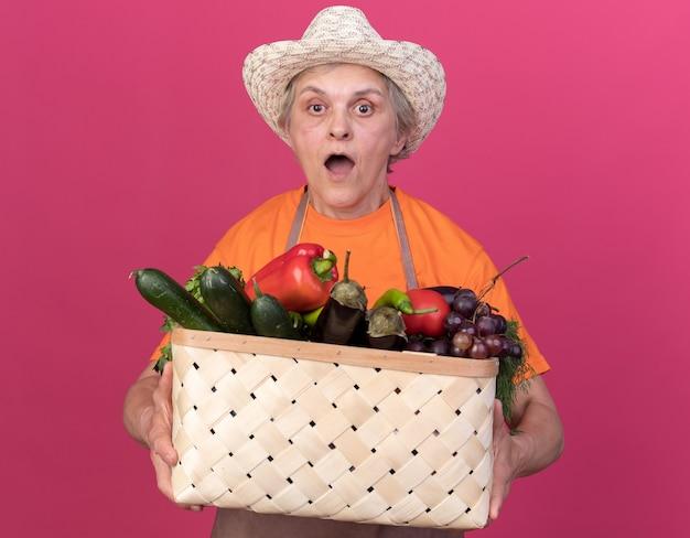 野菜のバスケットを保持しているガーデニング帽子をかぶって驚いた年配の女性の庭師