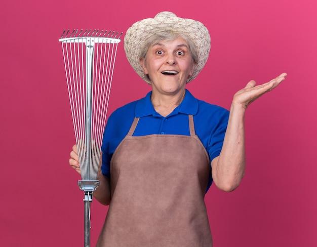 원예 모자를 쓰고 놀란 노인 여성 정원사는 잎 갈퀴를 잡고 손을 열어 둡니다.