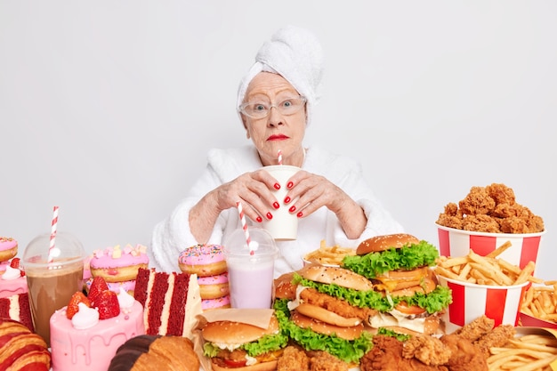 Surprised elderly lady with red lipstick has imbalancd nutrition eats different tasty junk food drinks cocktail containing much sugar dressed in domestic clothes
