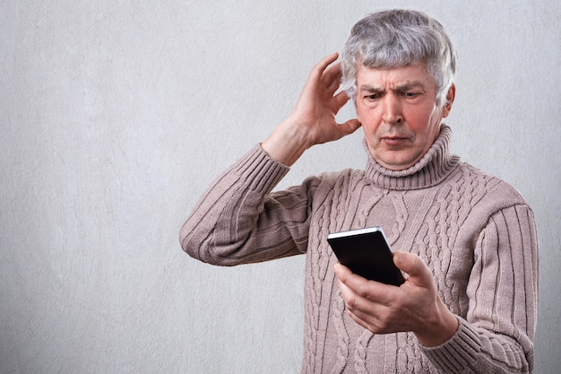 A surprised elderly man being shocked to watch news with his smartphone. worried senior man reading text message