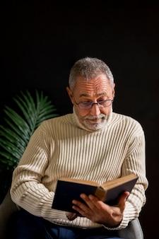 Surprised elderly man reading book