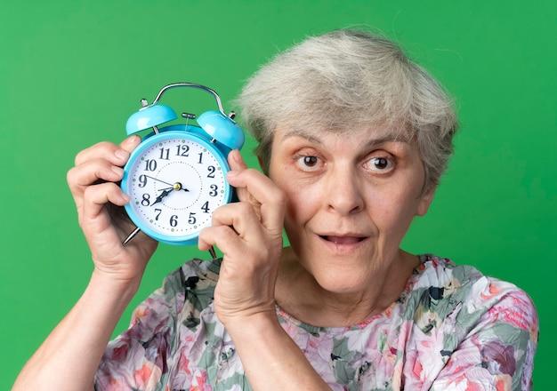 La donna anziana sorpresa tiene la sveglia vicino alla testa isolata sulla parete verde