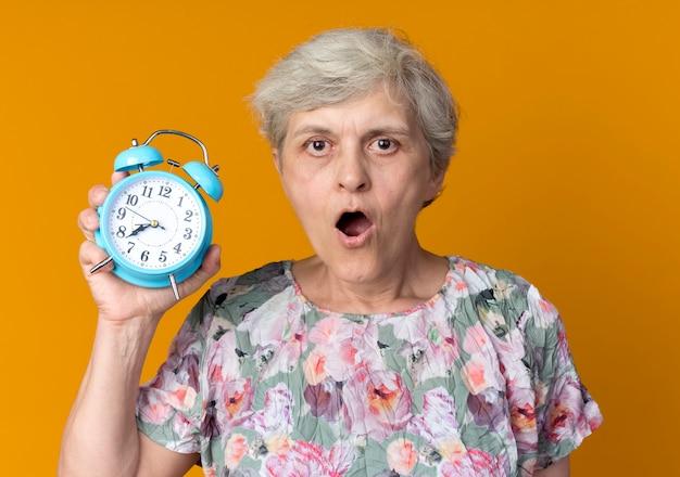 La donna anziana sorpresa tiene la sveglia isolata sulla parete arancione