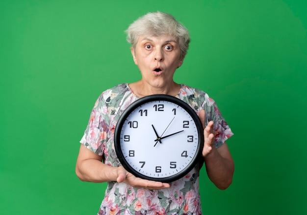 驚いた年配の女性は、緑の壁に隔離された時計を保持します