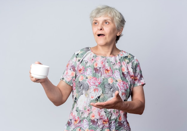 La donna anziana sorpresa tiene la tazza che guarda e che indica al lato isolato sulla parete bianca