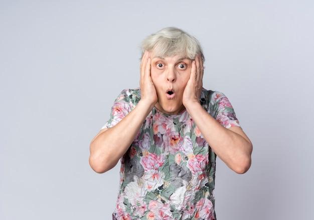 Удивленная пожилая женщина держит лицо руками, изолированными на белой стене