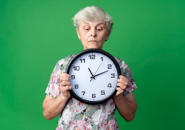 La donna anziana sorpresa tiene ed esamina l'orologio isolato sulla parete verde