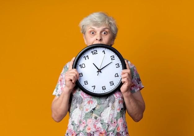 La donna anziana sorpresa tiene e guarda l'orologio isolato sulla parete arancione