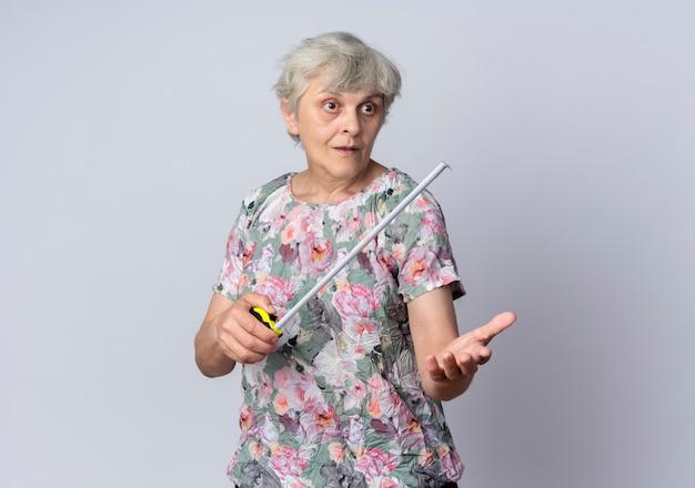 La donna anziana sorpresa tiene la misura di nastro che guarda e che indica in avanti isolato sulla parete bianca