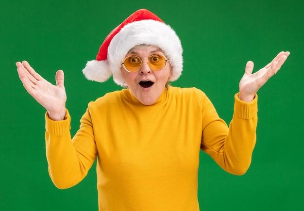 Удивленная пожилая женщина в солнцезащитных очках в шляпе санта-клауса, стоящая с поднятыми руками, изолированная на зеленой стене с копией пространства