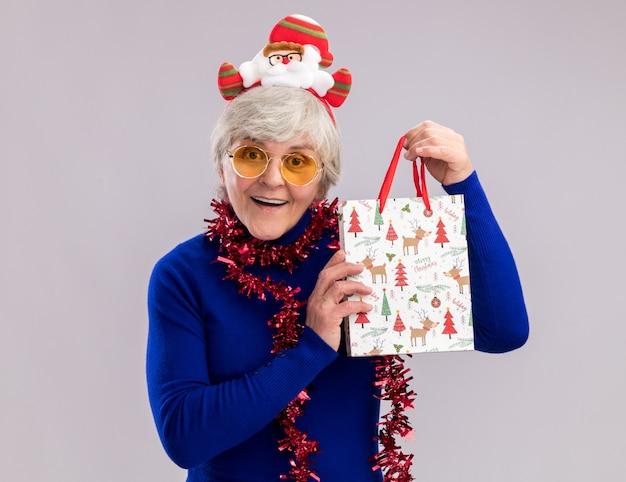 Удивленная пожилая женщина в солнцезащитных очках с ободком санта-клауса и гирляндой на шее держит бумажный подарочный пакет