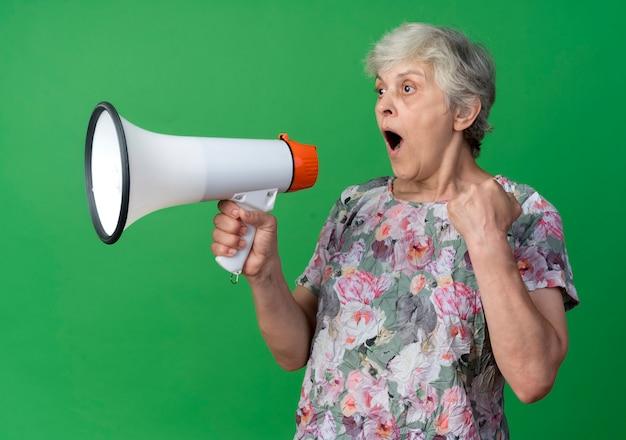 Удивленная пожилая женщина держит кулак и кричит в громкоговоритель, изолированную на зеленой стене