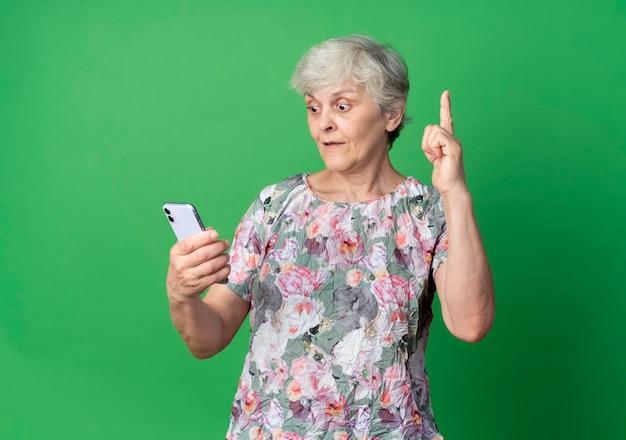 Удивленная пожилая женщина смотрит на телефон, указывая вверх, изолированный на зеленой стене