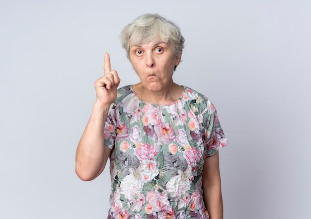 놀란 된 노인 여성 포인트에 고립 된 흰색 벽