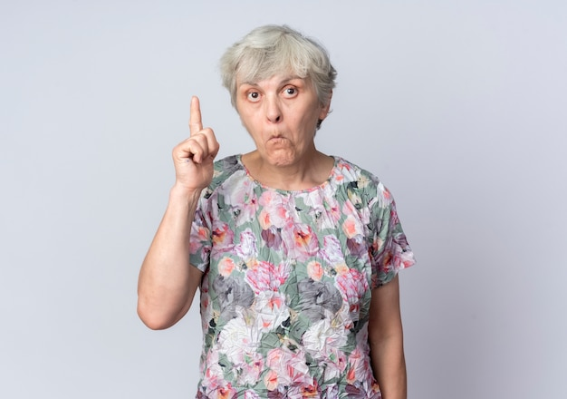 Surprised elderly woman points up isolated on white wall