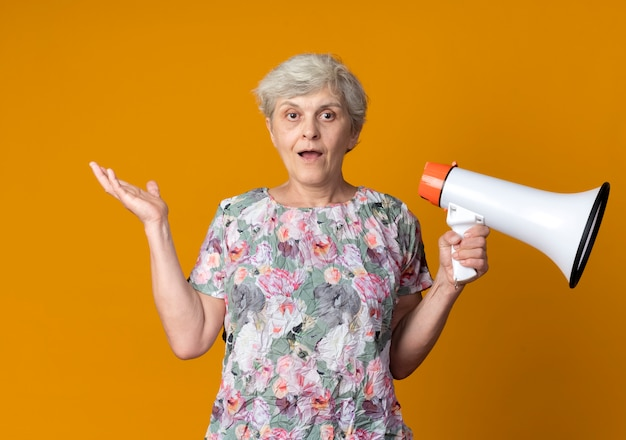 驚いた年配の女性がオレンジ色の壁に分離されたラウドスピーカーを持って手を上げる