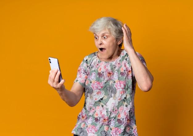 Удивленная пожилая женщина поднимает руку, глядя на телефон, изолированный на оранжевой стене