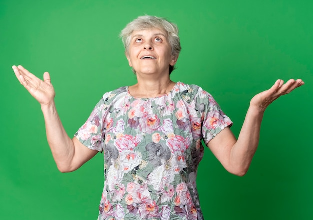 驚いた年配の女性が緑の壁に孤立して見上げる手を上げる