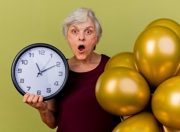 Удивленная пожилая женщина стоит с гелиевыми шарами и держит часы, изолированные на оливково-зеленой стене с копией пространства