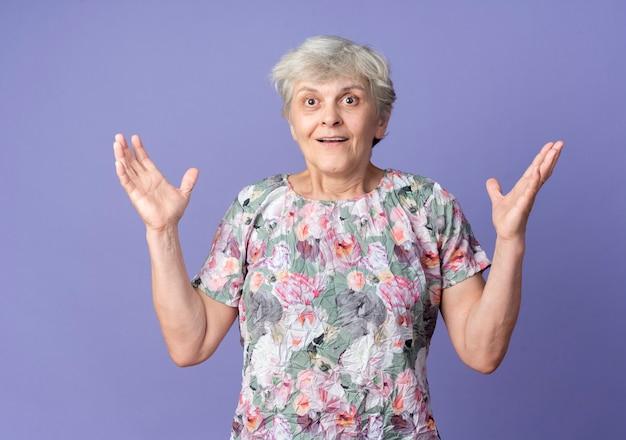 La donna anziana sorpresa sta con le mani alzate isolate sulla parete viola