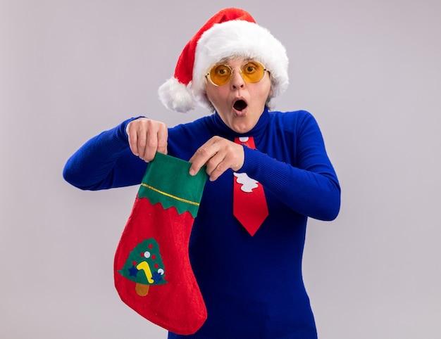 Donna anziana sorpresa in occhiali da sole con cappello da babbo natale e cravatta di babbo natale che tiene calza di natale isolata sul muro bianco con spazio per le copie