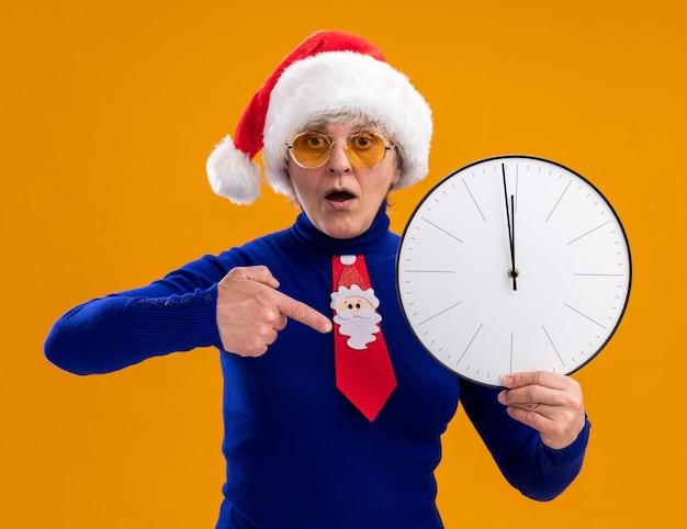 Donna anziana sorpresa in occhiali da sole con cappello da babbo natale e cravatta di babbo natale che tiene e indica l'orologio isolato sulla parete arancione con spazio di copia