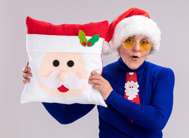 Surprised elderly woman in sun glasses with santa hat and santa tie holding santa pillow isolated on white wall with copy space