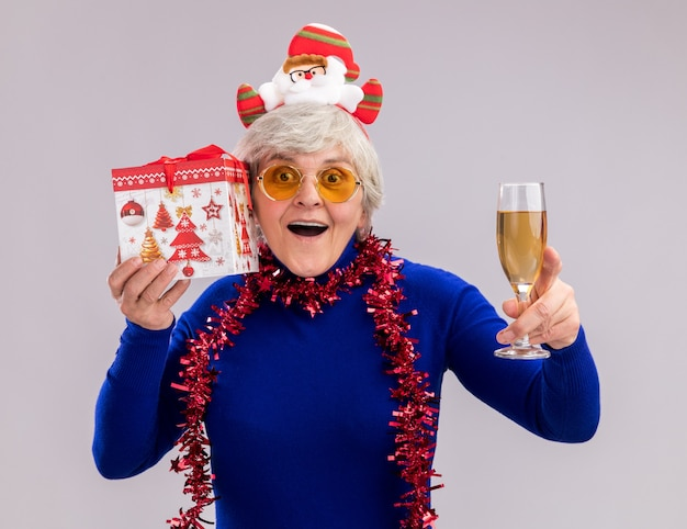 Surprised elderly woman in sun glasses with santa headband and garland around neck holds glass of champagne and christmas gift box isolated on white wall with copy space