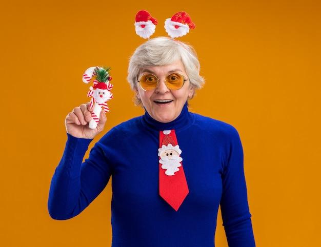 Donna anziana sorpresa in occhiali da sole con fascia santa e cravatta santa tenendo il bastoncino di zucchero isolato su sfondo arancione con spazio di copia