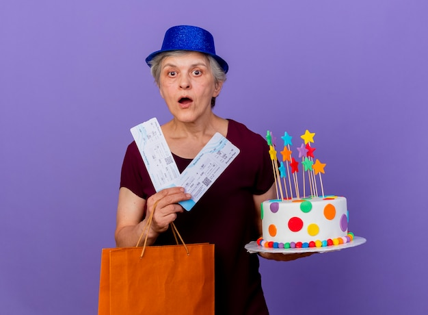 Surprised elderly woman wearing party hat holds airplane tickets paper shopping bag and birthday cake isolated on purple wall with copy space