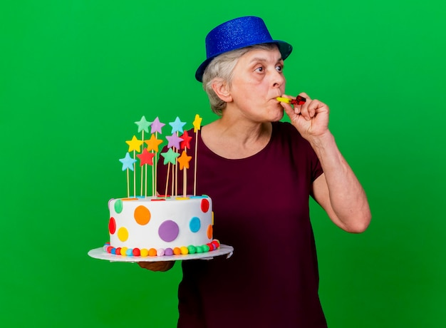 Surprised elderly woman wearing party hat holds birthday cake blowing whistle looking at side on green