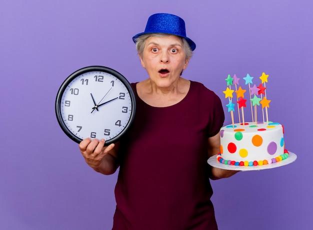 La donna anziana sorpresa che indossa il cappello del partito tiene l'orologio e la torta di compleanno isolata sulla parete viola con lo spazio della copia