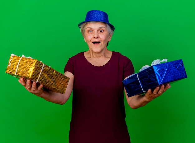 파티 모자를 쓰고 놀란 된 노인 여성 녹색에 선물 상자를 보유