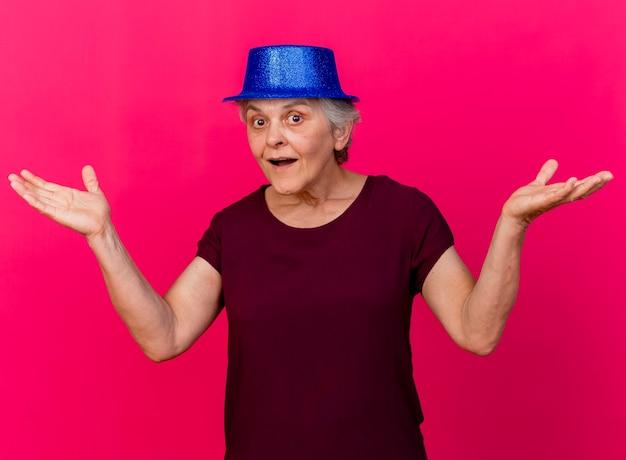 パーティーハットを身に着けている驚いた年配の女性は、ピンクの壁に隔離された手を開いて保持します。