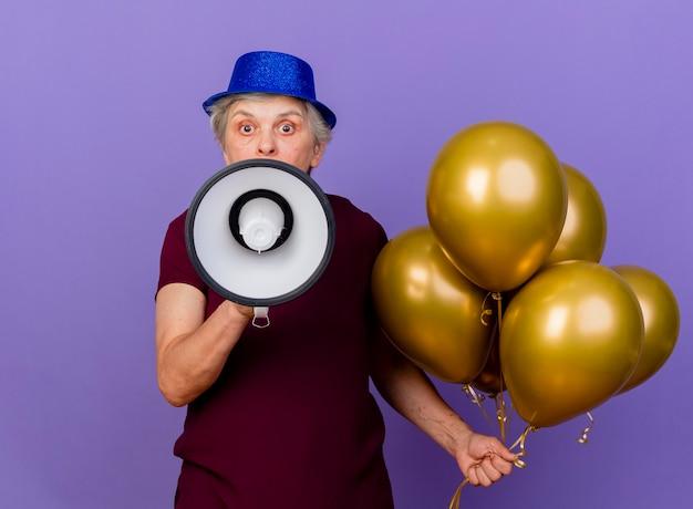 パーティーハットをかぶって驚いた年配の女性は、コピースペースと紫色の壁に隔離されたヘリウム気球とスピーカーを保持します。