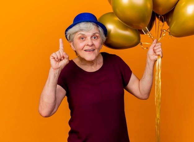 파티 모자를 쓰고 놀란 노인 여성 헬륨 풍선을 보유하고 복사 공간이 오렌지 벽에 고립 된 포인트