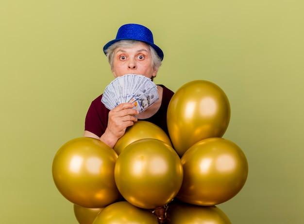 La donna anziana sorpresa che indossa il cappello del partito tiene i palloni dell'elio ed i soldi isolati sulla parete verde oliva con lo spazio della copia
